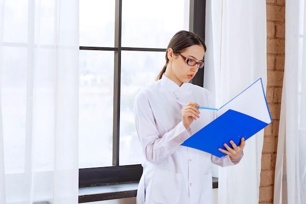 흰 코트를 입은 젊은 여성 의사가 창 근처에 있는 다음 환자에 대해 읽고 있습니다.