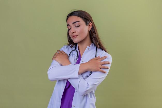 緑の孤立した背景の上に目を閉じて幸せと肯定的な自分を抱いてphonendoscopeと白衣の若い女性医師