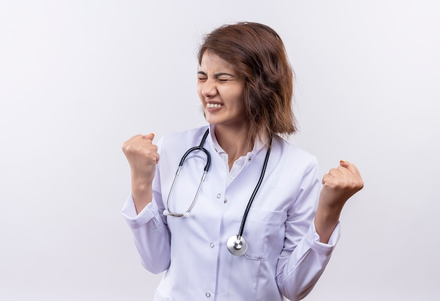 Молодая женщина-врач в белом халате со стетоскопом, сжимая кулаки с раздраженным выражением лица