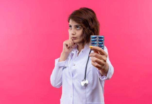 얼굴에 잠겨있는 표정으로 제쳐두고 찾고 약으로 물집을 들고 청진기와 흰색 코트에 젊은 여자 의사