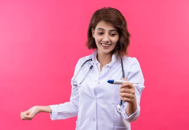 Молодая женщина-врач в белом халате со стетоскопом, держащая цифровой термометр, глядя на него, весело улыбаясь