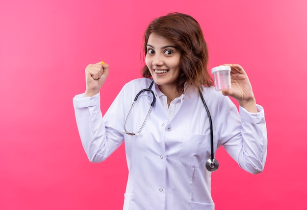 Молодая женщина-врач в белом халате со стетоскопом, держащая тестовую банку, сжимая кулак, счастлива и вышла