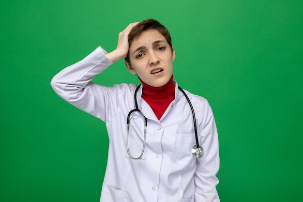 聴診器と白衣を着た若い女性医師は、間違いのために彼女の頭に手をつないで混乱しているように見えます