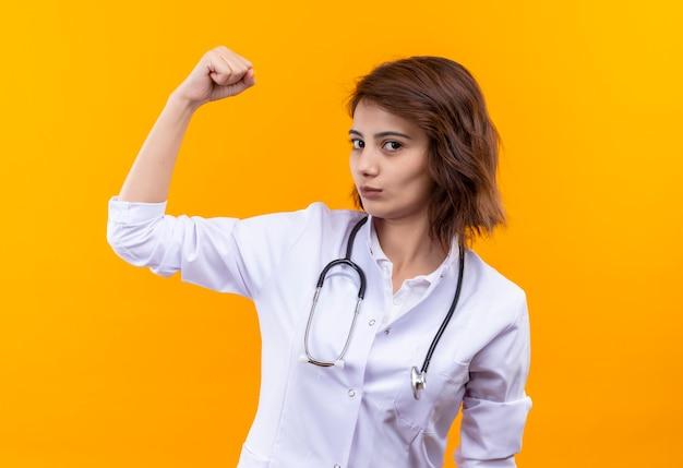 オレンジ色の壁の上に立って自信を持って上腕二頭筋を示す聴診器の拳を上げている白いコートの若い女性医師