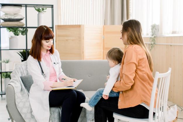 Доктор молодой женщины в белом сочинительстве пальто что-то в тетради и матери с ребёнком дома. концепция медицины, здравоохранения, педиатрии и людей