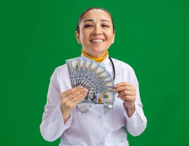 녹색 벽 위에 서 행복한 얼굴로 현금을 들고 목에 청진기와 흰색 의료 코트에 젊은 여자 의사