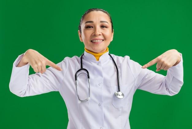 목 주위에 청진기와 흰색 의학 코트에 젊은 여자 의사 녹색 벽 위에 서있는 자신에 손가락으로 가리키는 자신감을 찾고 웃고