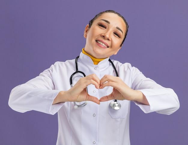 白い薬のコートを着た若い女性医師が、首に聴診器を付けて、紫色の壁の上に立って陽気に笑う指で心のジェスチャーをする