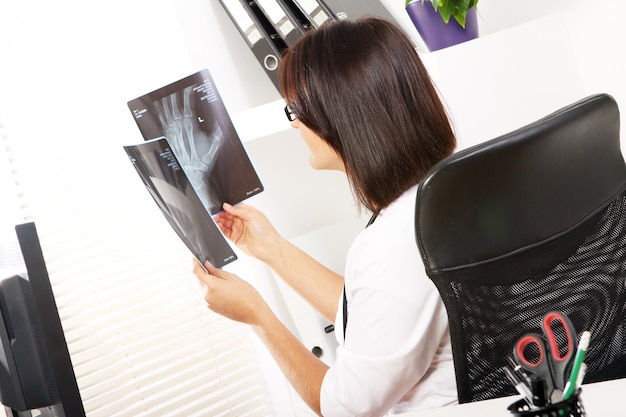 Young woman doctor is looking at xray