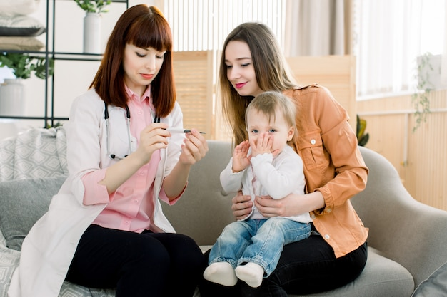 Доктор молодой женщины измеряя температуру ребёнка. доктор, измеряющий температуру ребенка