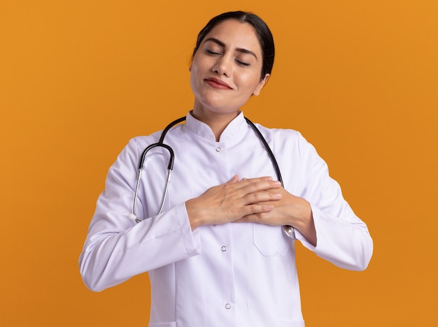 Young woman doctor in medical coat with stethoscope around her neck holding hands on her chest with closed eyes feeling thankful standing over orange wall