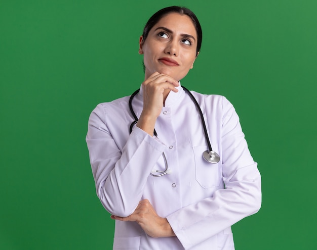 Young woman doctor in medical coat with stethoscope around her neck looking up with pensive expression thinking standing over green wall