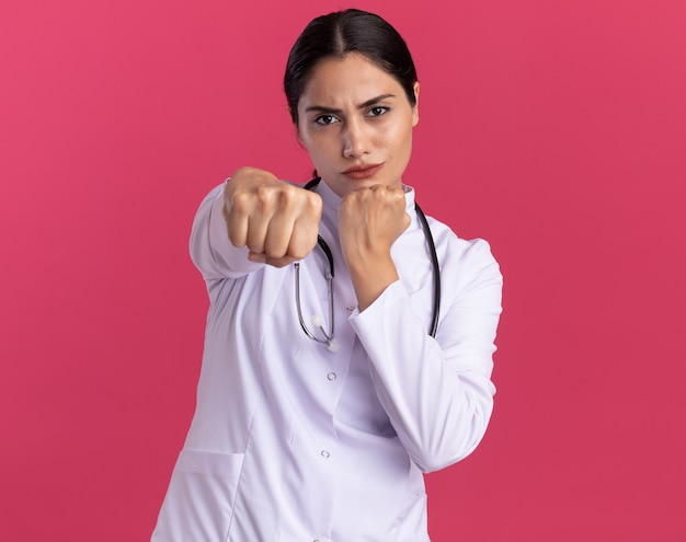 Giovane donna medico in cappotto medico con uno stetoscopio guardando davanti con faccia seria che mostra i pugni serrati davanti in piedi sopra il muro rosa