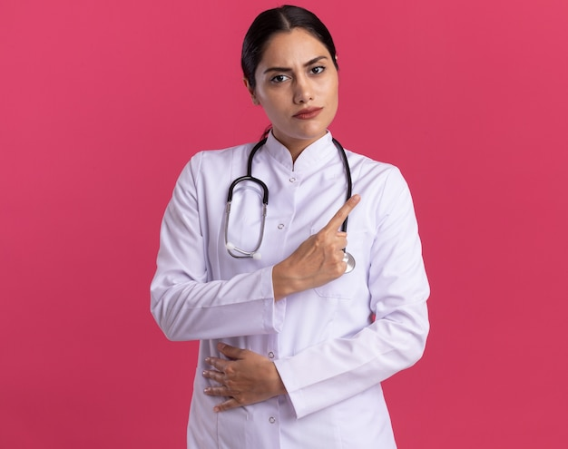 Medico della giovane donna in cappotto medico con lo stetoscopio che guarda davanti con la faccia seria che mostra l'avvertimento del dito indice che sta sopra la parete rosa