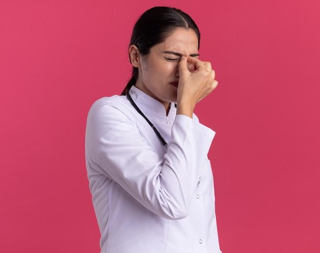 Medico della giovane donna in cappotto medico con lo stetoscopio che tocca il naso tra gli occhi chiusi con espressione infastidita in piedi sopra la parete rosa Foto Gratuite