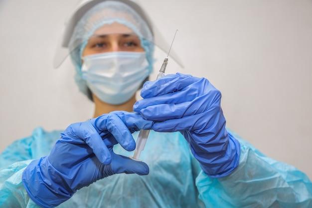 彼女の手に注射器を持つ保護マスクの若い女性医師看護師