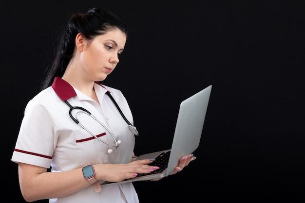 Молодая женщина-врач или медсестра, держащая портативный компьютер