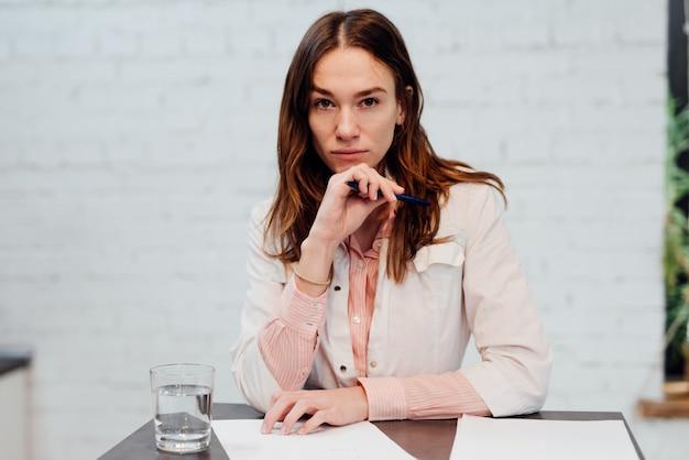 若い女性医師が彼女の机に座っています。