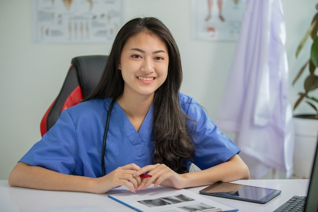 Young woman doctor smiling and working at office