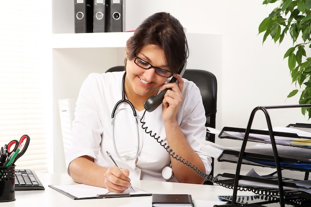 Young woman doctor talking by phone