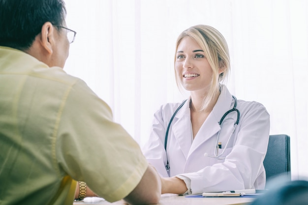 Young woman doctor talking with old man patient on desk