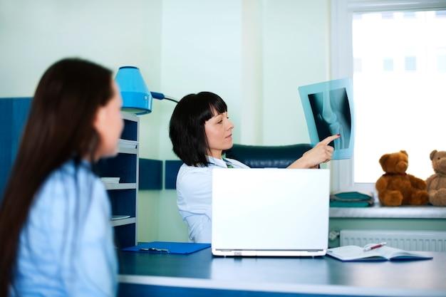 Giovane donna e medico guardando i raggi x