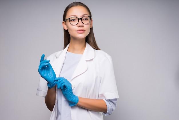 파란 장갑을 끼고 안경을 쓴 젊은 여성 의사가 카메라를 열심히 쳐다봅니다. 회색 배경에 고립