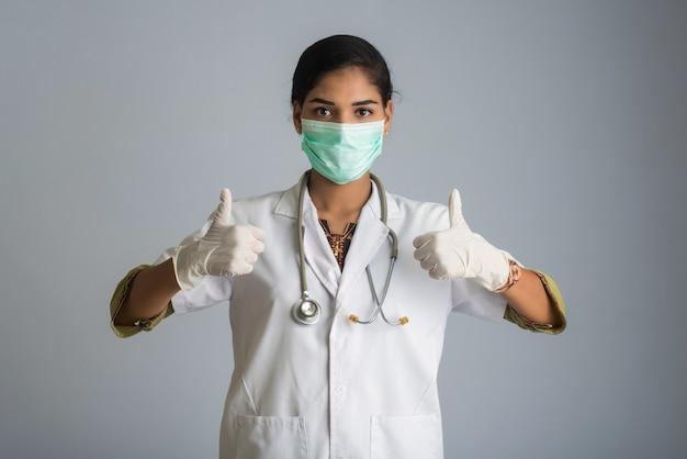 Доктор молодой женщины нося медицинский лицевой щиток гермошлема показывая большие пальцы руки вверх. женщина доктора нося хирургическую маску для вируса короны.