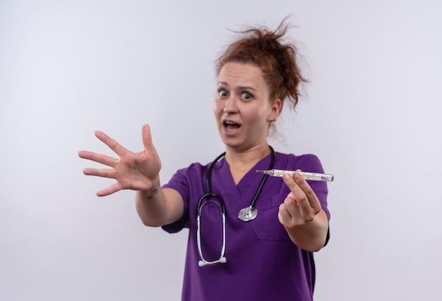 Medico della giovane donna che indossa l'uniforme medica con lo stetoscopio che tiene il termometro spaventato gridando in preda al panico in piedi sul muro bianco