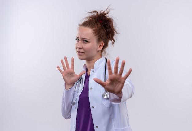청진기와 흰색 코트를 입고 젊은 여자 의사가 흰 벽 위에 서있는 손으로 정지 신호를 만드는 걱정