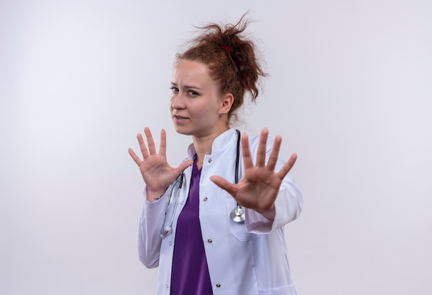 Young woman doctor wearing white coat with stethoscope worried making stop sign with hands standing over white wall