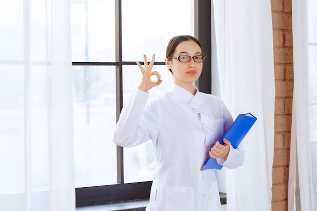 Young woman doctor in white coat holding binder in her hands near the window.