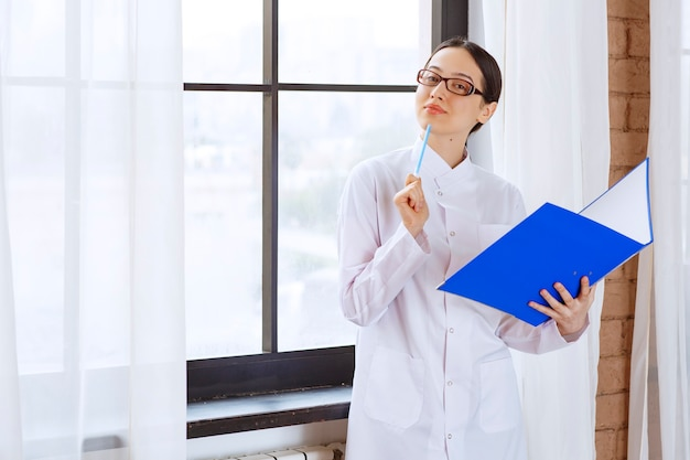 Young woman doctor in white coat holding blue binder and pen near the window.