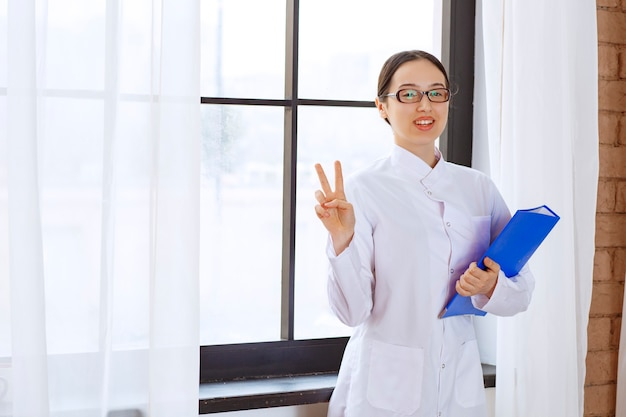 Young woman doctor in white coat posing with blue binder near the window.