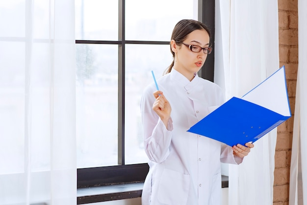 Young woman doctor in white coat reading about next patient near the window.