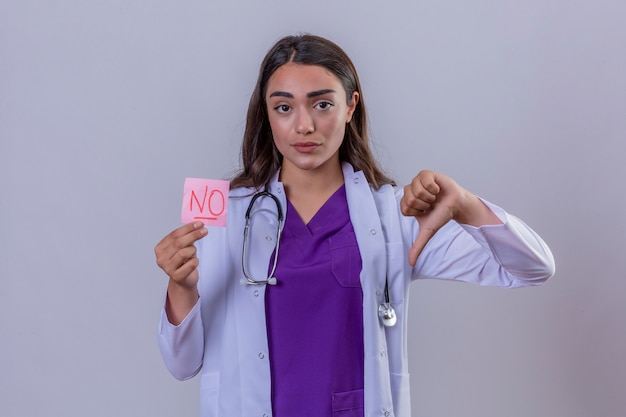 Young woman doctor in white coat with phonendoscope holding reminder paper with no message showing dislike with thumbs down over isolated white background
