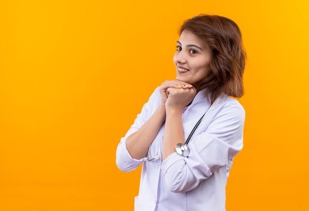 Medico della giovane donna in camice bianco con lo stetoscopio che sembra uscito e felice che tiene insieme le braccia in attesa di sorpresa