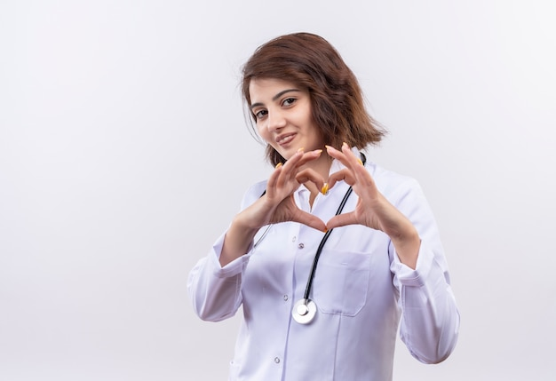Young woman doctor in white coat with stethoscope making heart gesture with fingers over chest smiling  standing over white wall