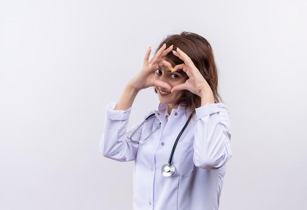Medico della giovane donna in camice bianco con lo stetoscopio che fa il gesto del cuore con le dita sul viso guardando attraverso le dita sorridenti in piedi sul muro bianco