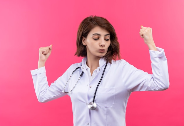 Young woman doctor in white coat with stethoscope raising fists showing biceps like winner standing over pink wall