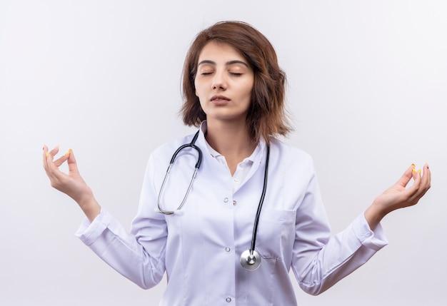 Medico della giovane donna in camice bianco con lo stetoscopio con gli occhi chiusi che si rilassa facendo il gesto di meditazione con le dita che stanno sopra il muro bianco