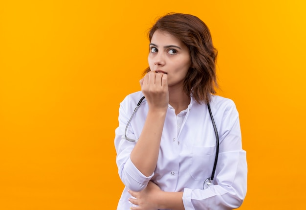 Young woman doctor in white coat with stethoscope worried and nervous biting nails standing over orange wall