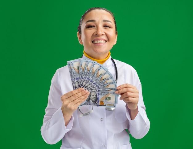 Medico della giovane donna in camice bianco medico con lo stetoscopio intorno al collo che tiene contanti con la faccia felice che sta sopra la parete verde