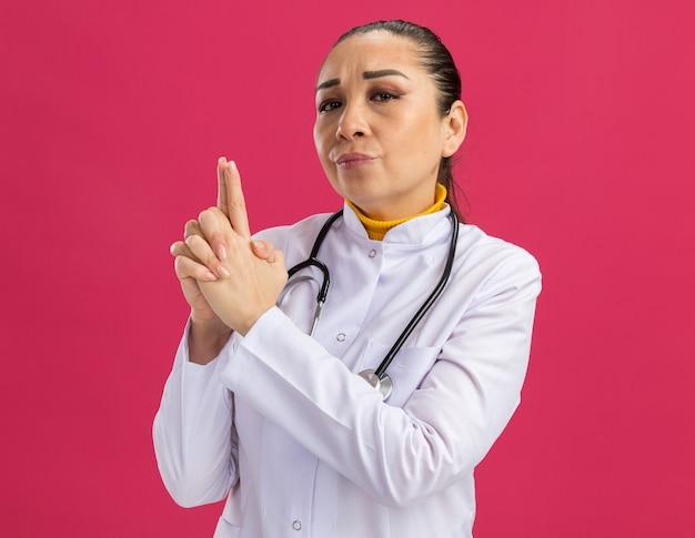 Medico della giovane donna in camice bianco della medicina con lo stetoscopio intorno al collo che sembra sicuro che fa il gesto della pistola con le dita che stanno sopra la parete rosa