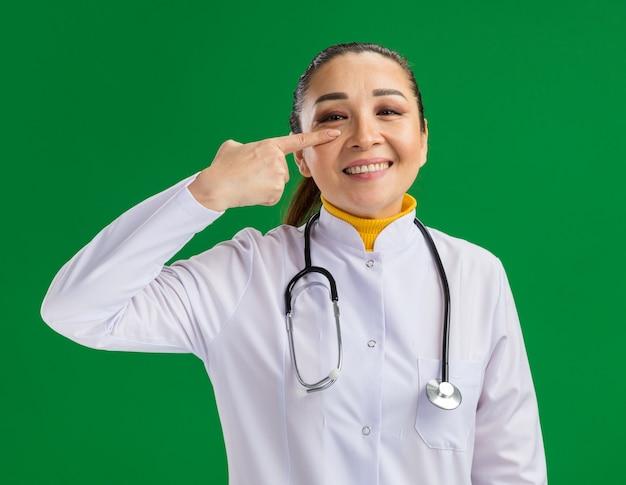 Medico della giovane donna in camice bianco della medicina con lo stetoscopio intorno al collo che indica con il dito indice al suo occhio che sorride allegramente che sta sopra la parete verde