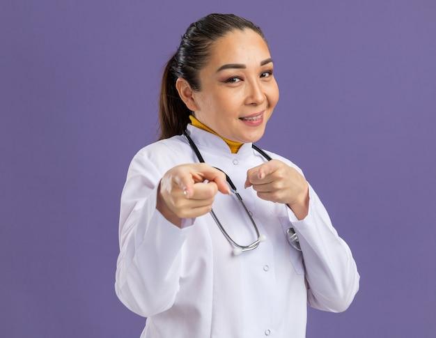 Medico della giovane donna in camice bianco della medicina con lo stetoscopio intorno al collo che sorride fiducioso che indica con i figners di indice che stanno sopra la parete viola