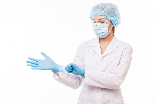 Young woman doctor in white uniform wearing mask and gloves isolated on white space