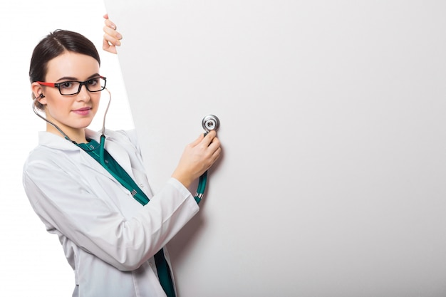 Young woman doctor with stethoscope and a blank billboard in white uniform