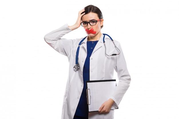 白い制服を着た白で録音された唇と彼女の手でクリップボードを保持している聴診器で若い女性医師