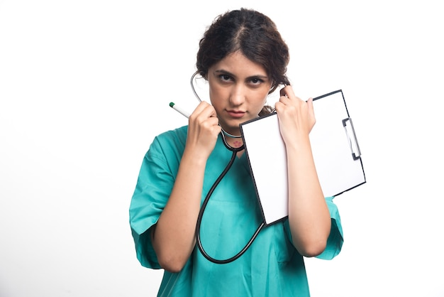 Medico della giovane donna con lo stetoscopio che tiene appunti in uniforme su priorità bassa bianca. foto di alta qualità